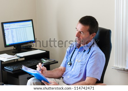 Doctor Writing On A Document In He's Practice - stock photo
