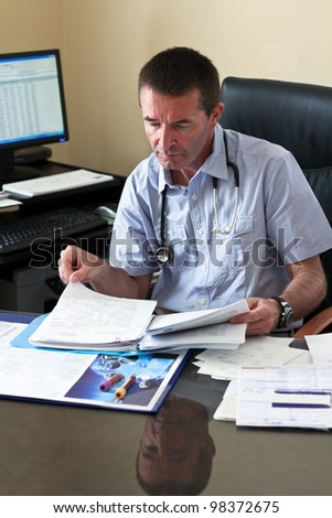 Doctor Writing On A Document In He's Practice
