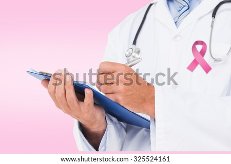 Doctor writing on clipboard against pink - stock photo