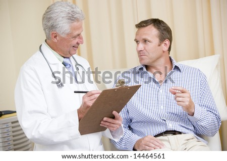 Doctor writing on clipboard while giving man checkup in exam room - stock photo