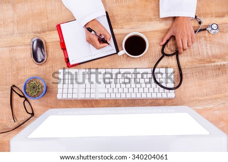 Doctor writing on her diary on desk - stock photo