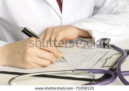doctor writing on the clipboard and stethoscope on the table