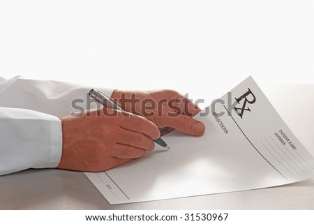 Doctor writing out prescription on RX form white background - stock photo