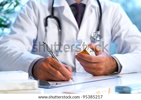 Doctor writing out RX prescription selective focus - stock photo