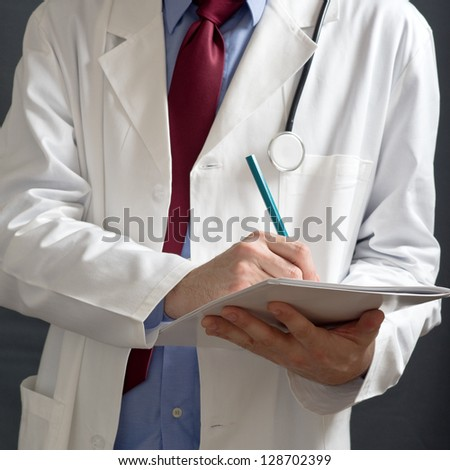 Doctor writing prescriptions. Health care professional writing. - stock photo