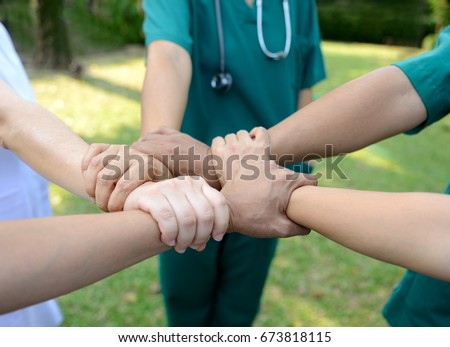 Doctors and nurses in a medical team stacking hands outdoor on the green park background (volunteer)