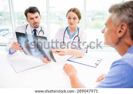 Doctors and patient discussing X-ray results in diagnostic center.