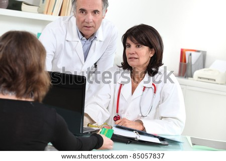 Doctors and patient sitting at a computer - stock photo