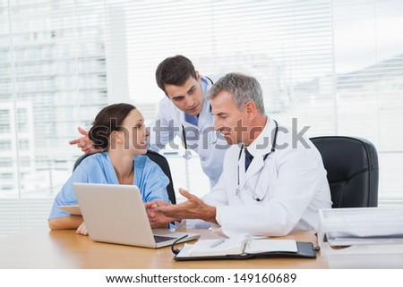 Doctors and surgeon discussing together in bright office - stock photo