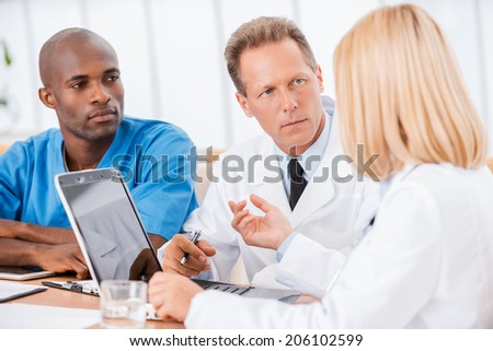 Doctors at the meeting. Three confident doctors discussing something while woman using computer and gesturing - stock photo