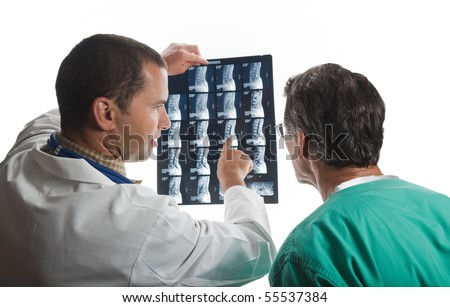 Doctors confer while examining film scans of patient's spine. - stock photo