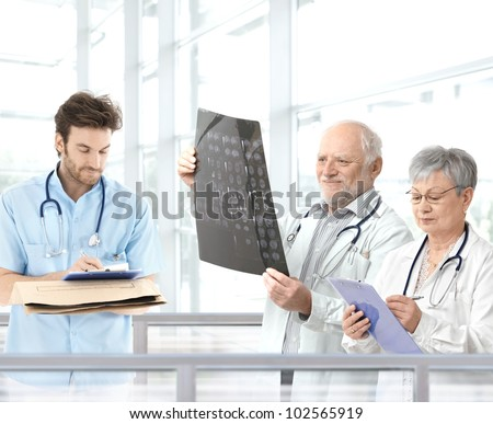 Doctors discussing diagnosis in hospital lobby, team lead by experienced professor.