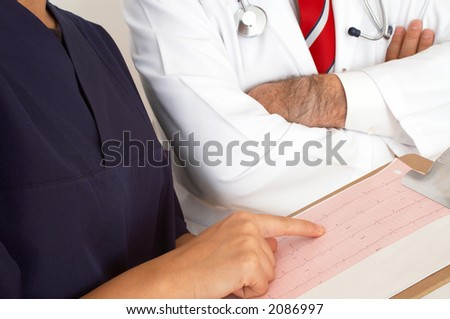 doctors examining printout of a heart monitor report - stock photo
