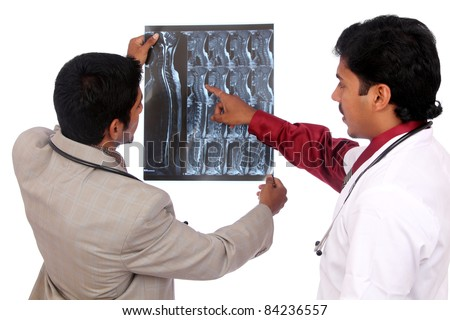 Doctors examining the X-ray over white.