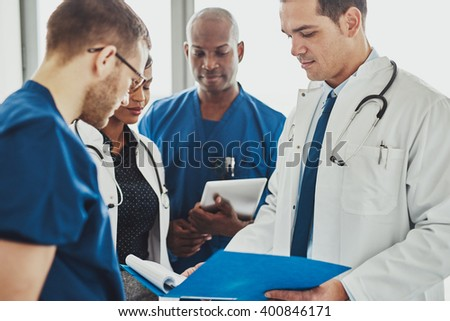 Doctors having a conversation looking at documents, mixed races, surgeons and doctors - stock photo