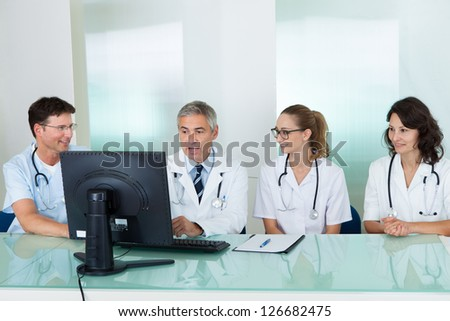 Doctors having a meeting seated at a table in front of a computer discussing case histories - stock photo
