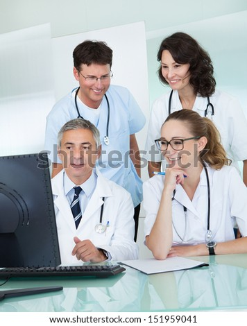 Doctors having a meeting seated at a table in front of a computer discussing case histories
