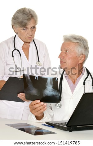 Doctors in a white coat with a stethoscope looking at xray - stock photo