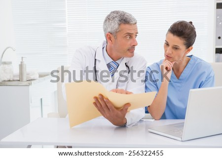 Doctors looking at files in medical office - stock photo