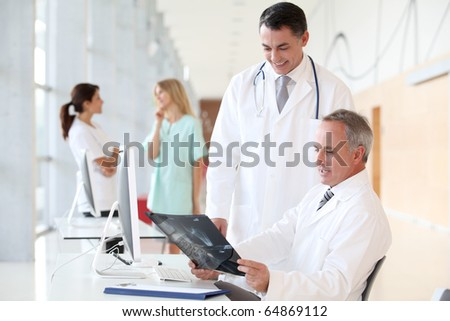 Doctors looking at radiography in hospital - stock photo