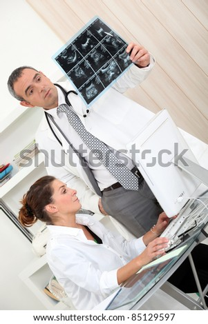 Doctors looking at x-rays - stock photo