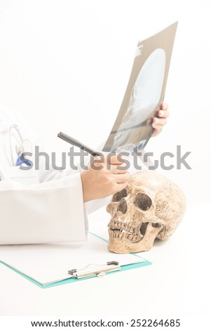 Doctors  looks at human skull. and Sheets X-ray services. on white background on white.   - stock photo