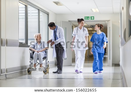Doctors & nurse in hospital corridor with senior female patient in wheel chair with male Asian doctor - stock photo