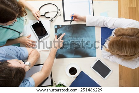 Doctors sitting around the table and interpreting x-ray image - stock photo