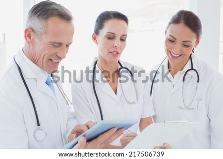 Doctors standing beside each other and using a tablet