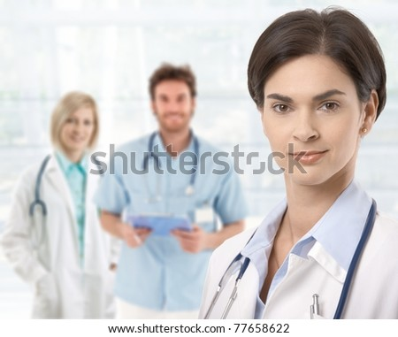Doctors standing in lobby, female doctor in front.?