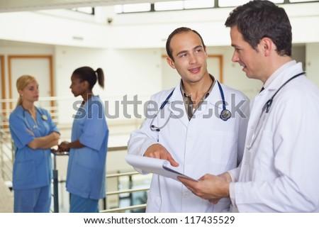 Doctors talking in hospital hallway - stock photo