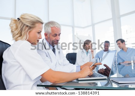 Doctors using a laptop in a bright office - stock photo