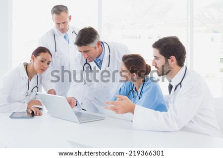 Doctors using a laptop together at work - stock photo