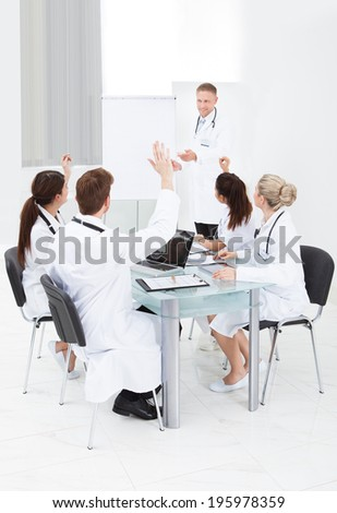 Doctors with hands raised answering colleague in meeting at clinic - stock photo