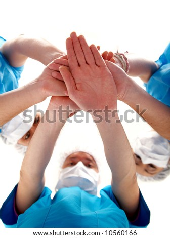 doctors with hands together to form a medical teamwork - isolated over a white background - stock photo