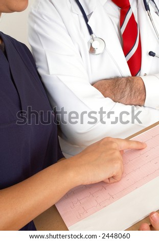doctors with heart monitor report, shallow dof - stock photo