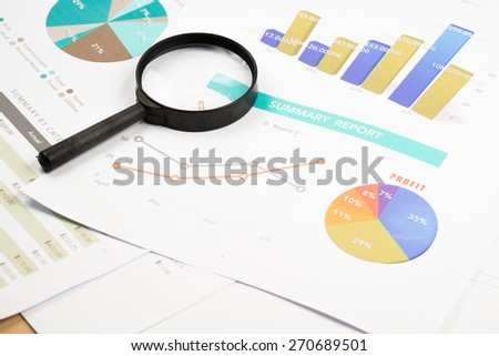 Document financial with magnifying glass.searching profit - stock photo