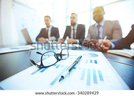 Document, pen and eyeglasses on background of working businessmen - stock photo