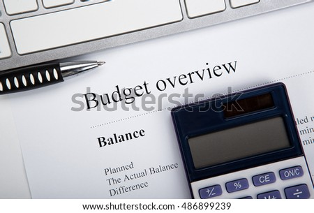 document with title budget overview and keyboard, calculator close up