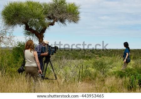 Documentary film crew, cameraman, photographer and actress - stock photo