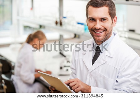 Documenting the result of experiments. Smiling young male scientist holding digital tablet and looking at camera while his female colleague working in the background - stock photo