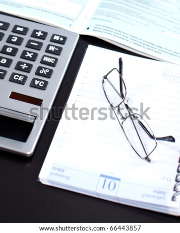 Documents, a  calculator, eyeglasses on the black table - stock photo