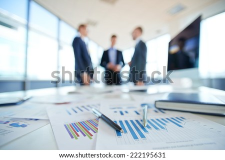 Documents on office table and three men talking in the background
