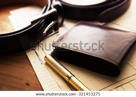Documents, pen, belt and a leather wallet on a wooden desk. hotel table or gentleman's desk. shallow depth of field. - stock photo