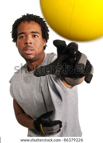 dodge ball player throwing a yellow ball at viewer - stock photo
