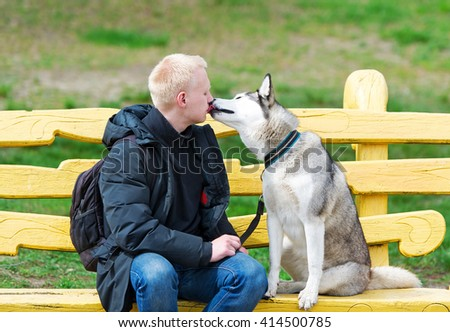 Dog and her trainer sit on a wooden bench in park. - stock photo