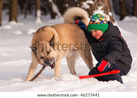 Dog and little boy playing in winter forest - stock photo