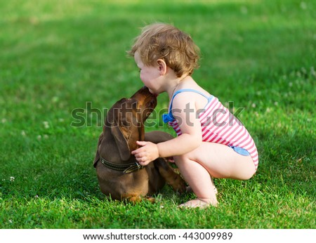 Dog and little girl. The dog licks a girl's face. - stock photo