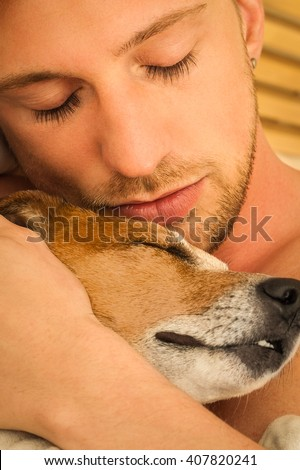 dog and owner in bed sleeping  close together and cuddling  - stock photo