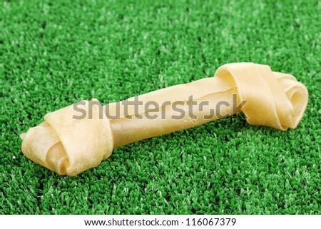 Dog bone on green grass - stock photo